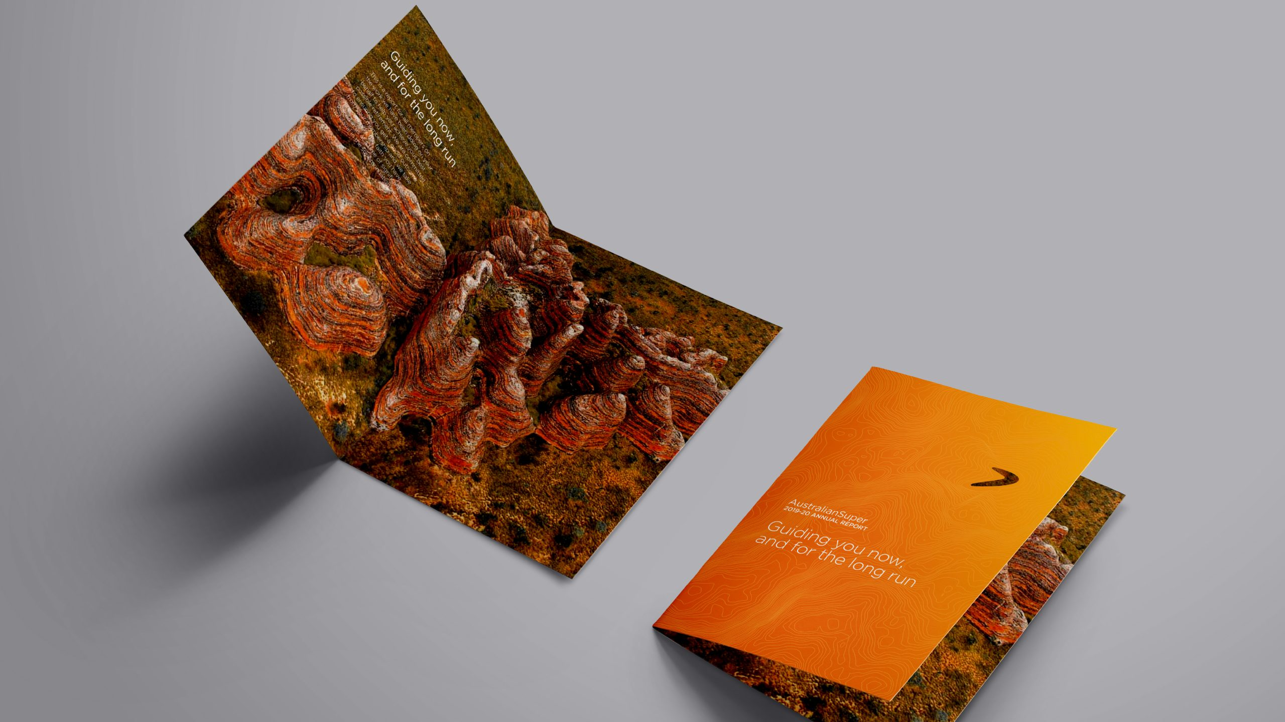 A flat lay image of the AustralianSuper 2019/2020 Annual Report. Includes aerial imagery of the Kimberley in Western Australia overlayed with topographic line work designed by Helium Design Melbourne.