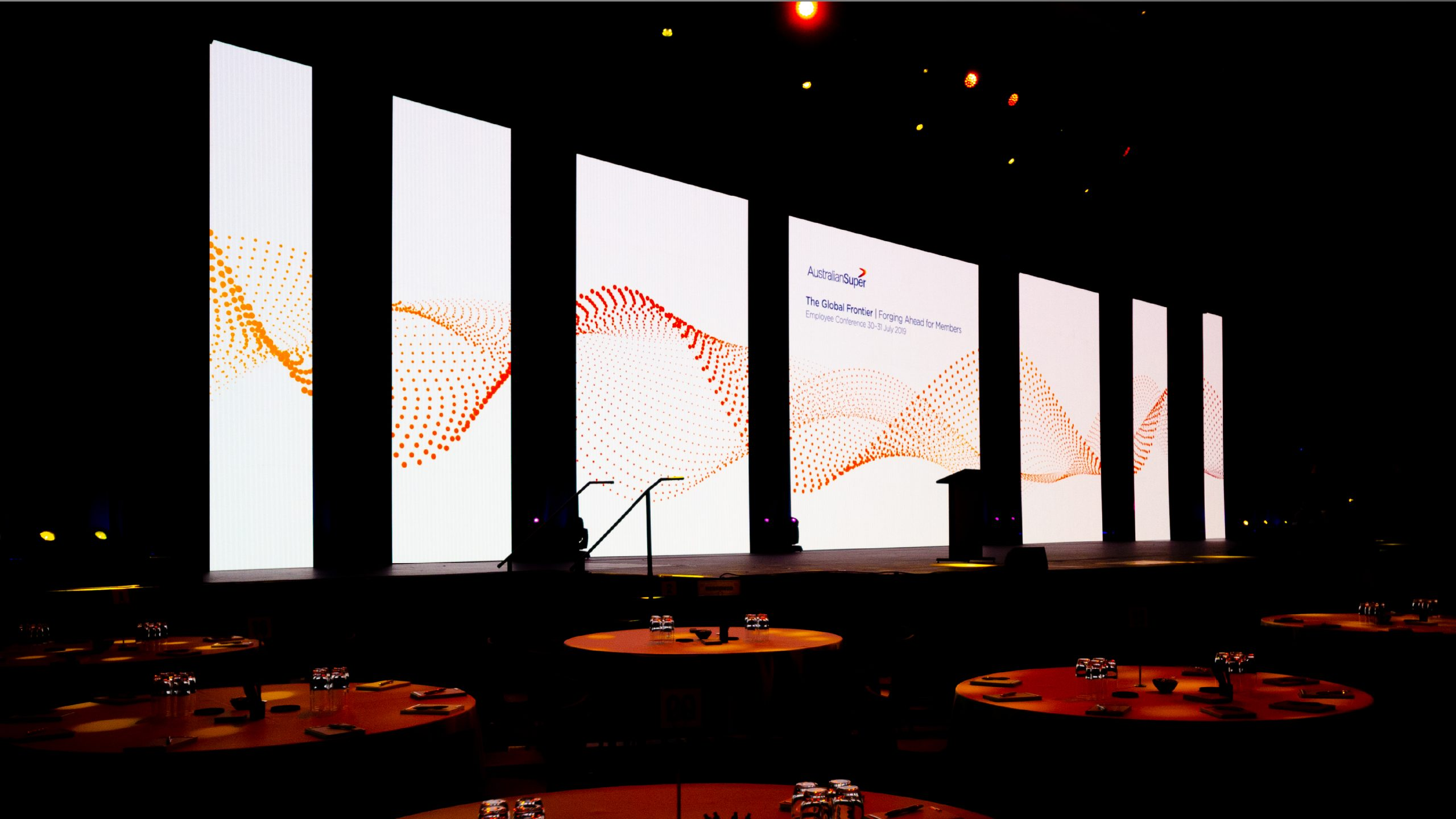 An array of large LED screens on a stage feature the AustralianSuper – Good to Great for Members branding.