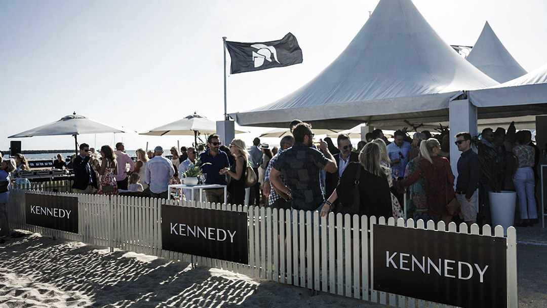 Kennedy beach polo tents featuring black flags with Kennedy branding.